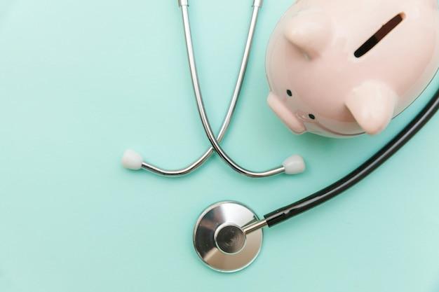 Stetoscopio dell'attrezzatura di medico della medicina o phonendoscope e porcellino salvadanaio isolati