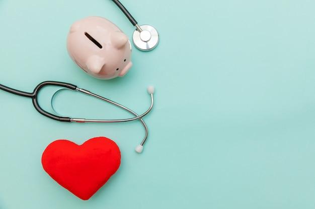 Stetoscopio dell'attrezzatura di medico della medicina o porcellino salvadanaio del phonendoscope e cuore rosso isolati su fondo blu pastello d'avanguardia