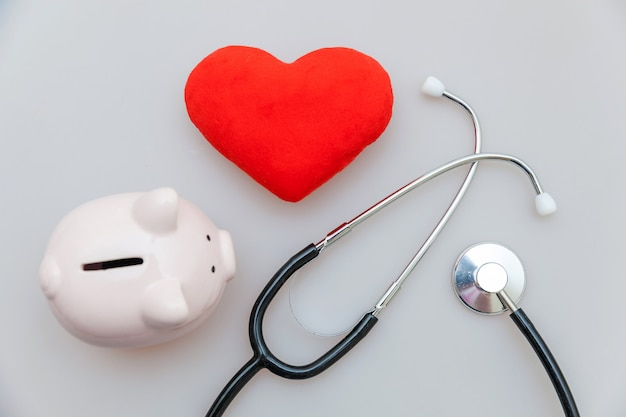 Stetoscopio dell'attrezzatura di medico della medicina o porcellino salvadanaio del phonendoscope e cuore rosso isolati