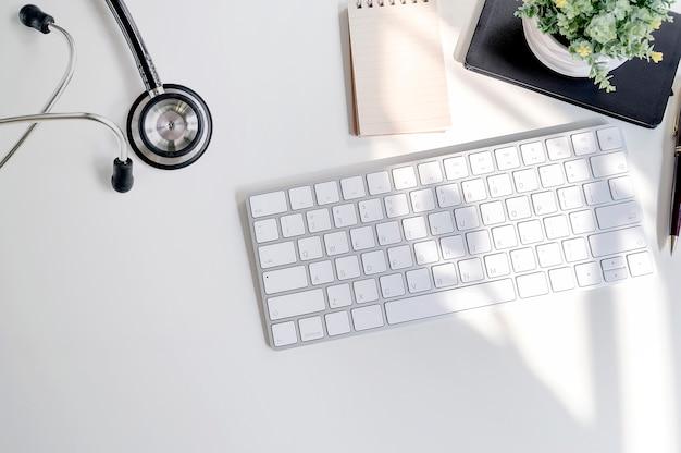 Stetoscopio di mockup con tastiera bianca e forniture sul tavolo bianco