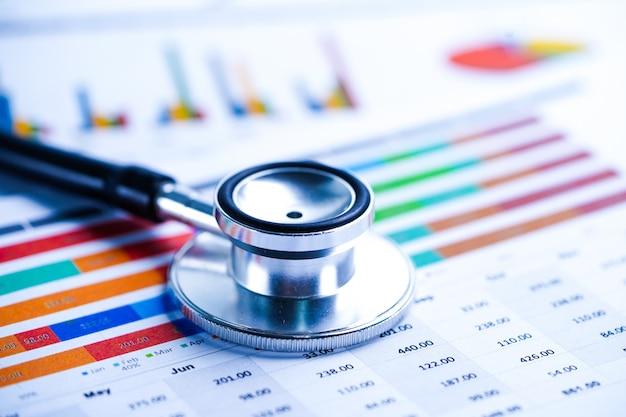 Stetoscopio, diagrammi e grafici diffondono fogli di carta