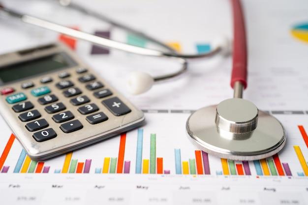 Stetoscopio e calcolatrice su carta millimetrata.