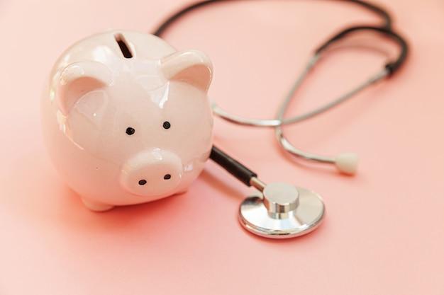 Stetoscopio e porcellino salvadanaio dell'attrezzatura di medico della medicina isolati su pastello rosa