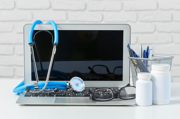Stetoscopio, laptop e pillole sul tavolo bianco