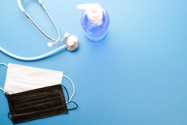 Stetoscopio, maschere mediche e gel antibatterico su un tavolo blu