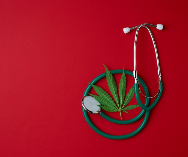 Stetoscopio medico e foglia verde della canapa su una priorità bassa rossa
