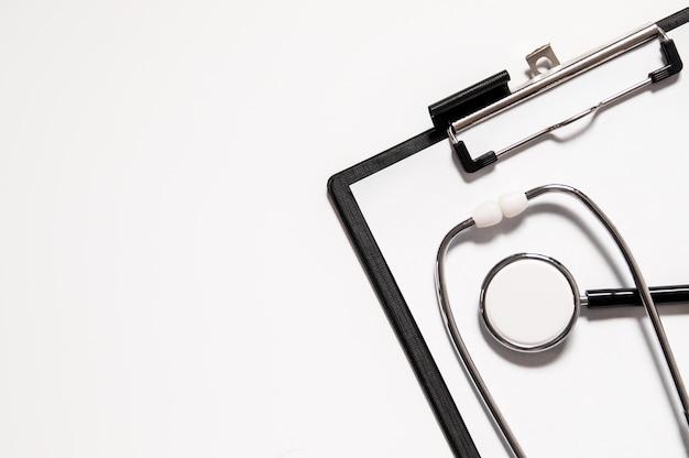 Stetoscopio medico o phonendoscope isolato su sfondo bianco tagliato fuori. stetoscopio e appunti con fogli bianchi in bianco e spazio di copia. concetto medico