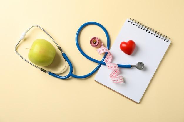 Stetoscopio, mela, taccuino, cuore e nastro di misurazione su sfondo giallo, spazio per il testo