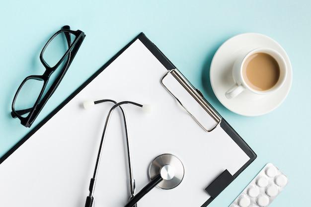Stetoscopio negli appunti con blister; occhiali e tazza di caffè sulla scrivania