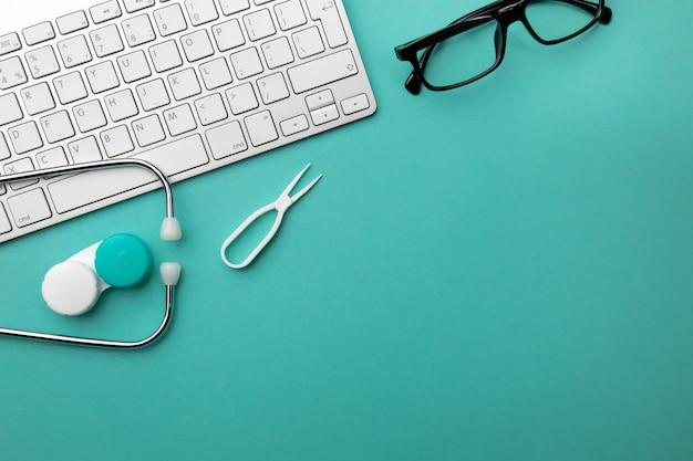 Stetoscopio nello scrittorio di medici con il taccuino, la penna, la tastiera, il topo e le pillole