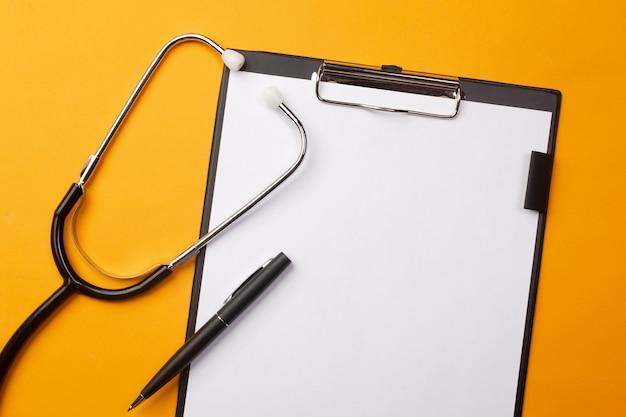 Stetoscopio nello scrittorio di medici con la compressa, la penna e le pillole