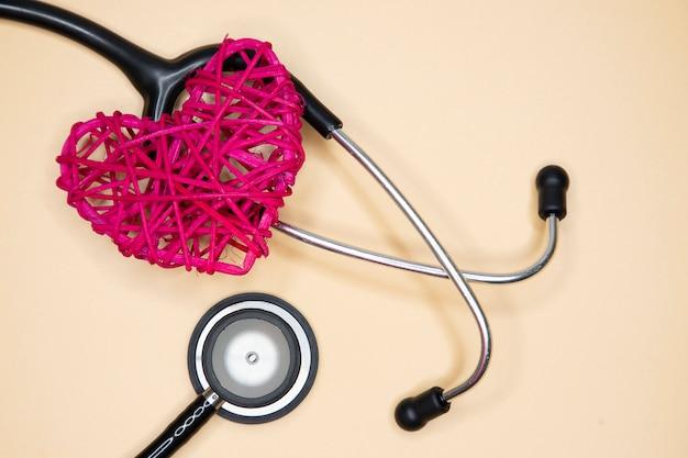 Stetoscopio nero e cuore rosso rattan