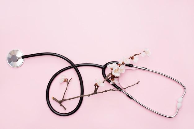 Stetoscopio piatto con ramo di primavera in fiore sul rosa