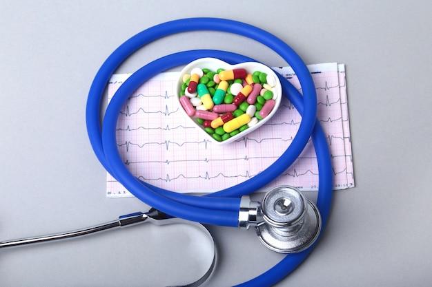 Stetoscopio, prescrizione rx e assortimento di pillole colorate e capsule sul piatto.