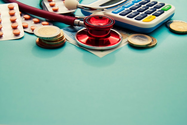 Stetoscopio rosso su un mucchio di monete, pillole sul blu. copyspace. medicina e assistenza sanitaria.