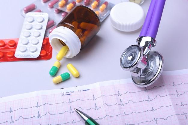 Stetoscopio sdraiato su prescrizione rx con pillole assortite. vita sana o concetto di assicurazione.