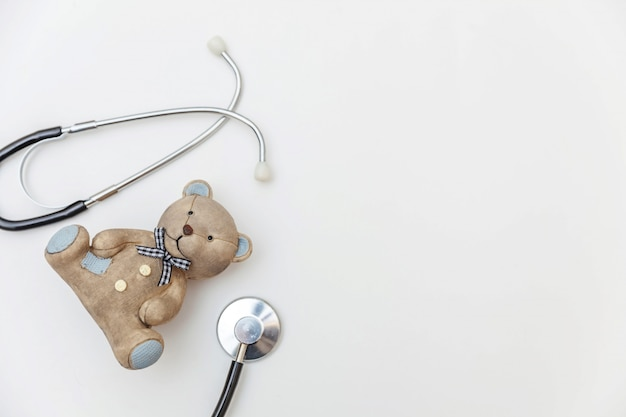 Stetoscopio semplicemente minimalista dell'orso del giocattolo di progettazione e dell'attrezzatura della medicina isolato su fondo bianco. concetto di medico dei bambini di sanità. simbolo pediatra vista piana, vista dall'alto
