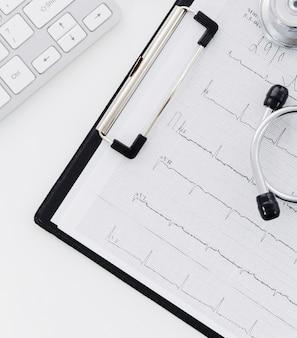 Stetoscopio su elettrocardiografo sopra la lavagna per appunti e laptop su sfondo bianco