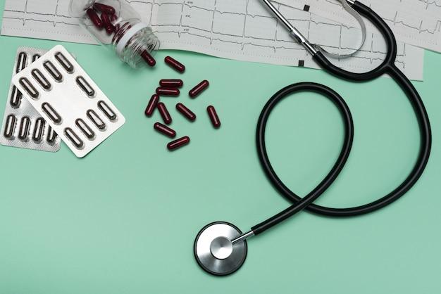 Stetoscopio su un elettrocardiogramma con capsule su uno sfondo verde. elettrocardiogramma con stetoscopio nero
