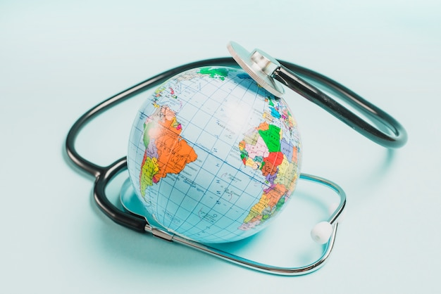 Stetoscopio sul globo su sfondo blu