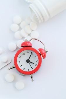 Stetoscopio, sveglia e primo piano bianco delle pillole. assistenza sanitaria