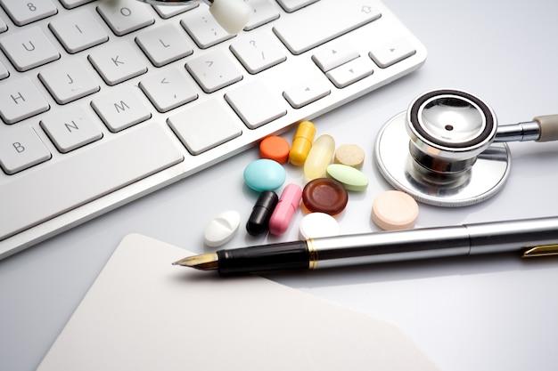 Stetoscopio, tastiera e pillole su sfondo nero