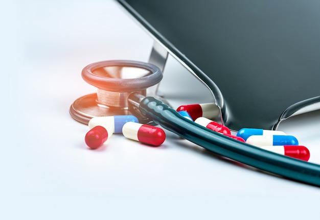 Stetoscopio verde con il mucchio delle pillole della capsula antibiotica sulla tavola bianca vicino al vassoio della droga