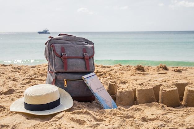 Stile di viaggio zaino con cappello di paglia, borsa e mappa su una spiaggia tropicale