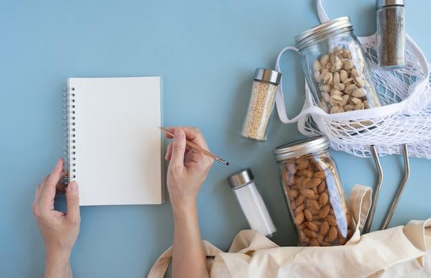 Stile di vita a spreco zero. borsa a rete in cotone con dado, spezie in vaso di vetro sostenibile e paglia riutilizzabile su fondo piatto blu.