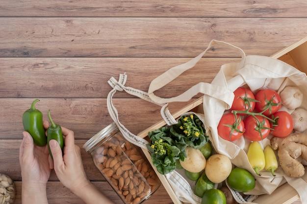 Stile di vita a spreco zero. sacchetto di rete di cotone con verdure fresche sul tavolo di legno piatto lay. senza plastica per l'acquisto e la consegna di prodotti alimentari.