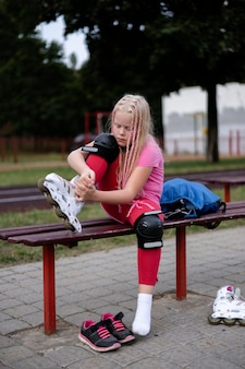 Stile di vita attivo in una città moderna, la ragazza mette su pattini a rotelle allo stadio