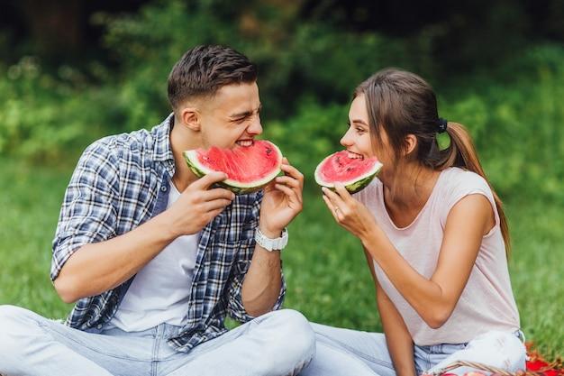 Stile di vita! coppia in buona salute. divertirsi mangiando cucinando insieme. belle giovani coppie sane con alimento sano. anguria ed estate.