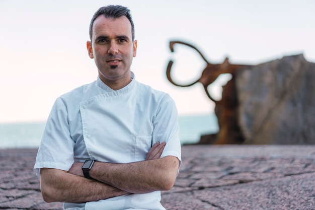 Stile di vita di un cuoco, chef sorridente caucasico con grembiule bianco in una foto sulla costa