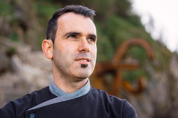 Stile di vita di un cuoco, ritratto di giovane uomo dai capelli scuri vestito da chef con grembiule nero