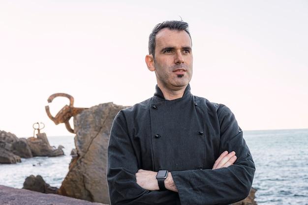 Stile di vita di un cuoco, ritratto di giovane uomo dai capelli scuri vestito da chef in grembiule nero