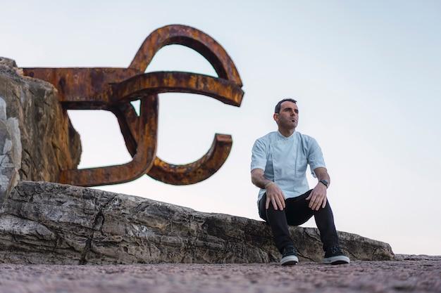 Stile di vita di un cuoco, ritratto di un giovane seduto in un grembiule bianco in una foto sulla costa