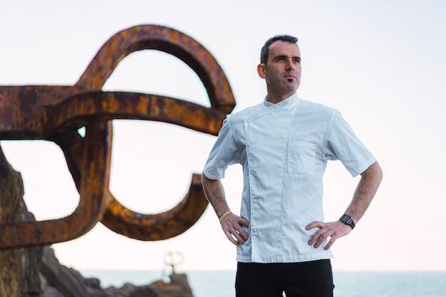 Stile di vita di un cuoco, un giovane uomo in un grembiule bianco in una foto sulla costa