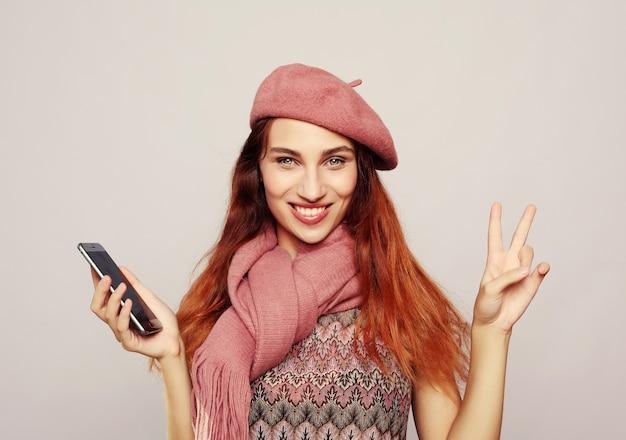 Stile di vita e concetto della gente del ritratto di una ragazza casuale soddisfatta che tiene telefono cellulare