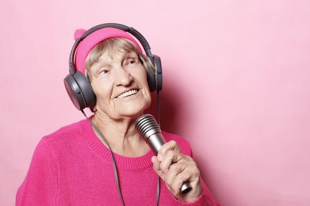 Stile di vita e persone: divertente vecchia signora che ascolta la musica con le cuffie e canta con il microfono