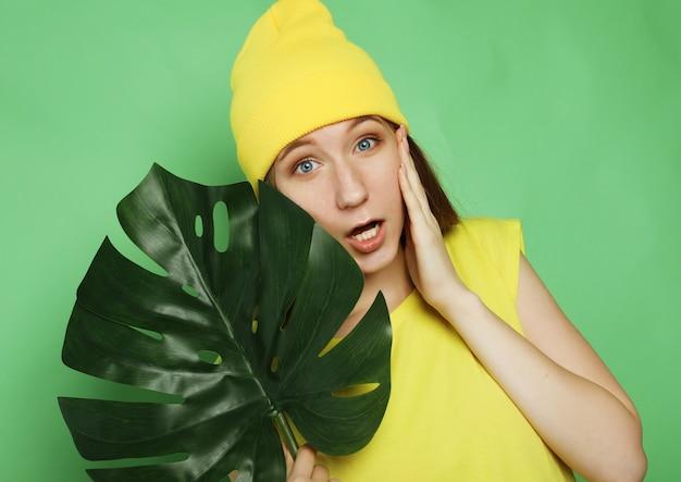 Stile di vita, emozione e concetto di persone: giovane bella donna che indossa abiti casual gialli, tenendo la foglia di monstera