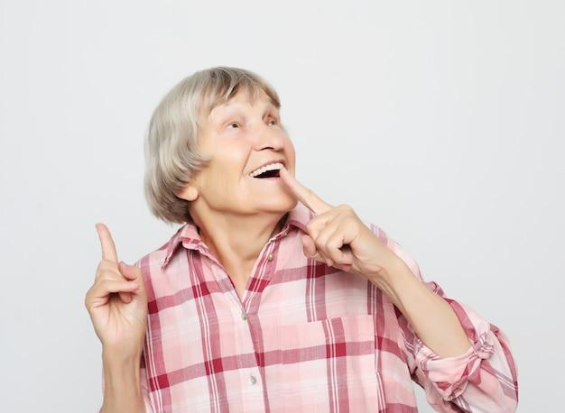 Stile di vita, emozione e concetto di persone: nonna invecchiata con la faccia scioccata. ritratto di nonna con camicia rosa.