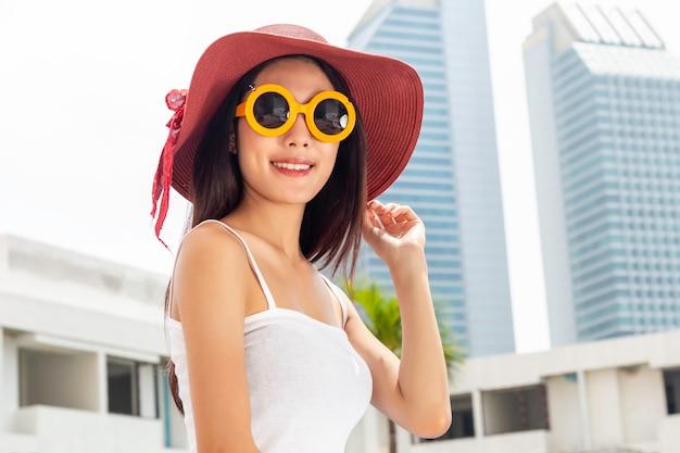 Stile di vita estivo ritratto asiatico di ragazza carina in piedi in città.