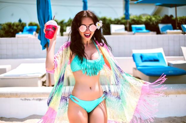 Stile di vita luminoso ritratto di uscito giovane donna bruna ballare e divertirsi al resort tropicale, tenendo una gustosa limonata dolce, indossando bikini stile boho e kimono, rilassarsi e viaggiare.