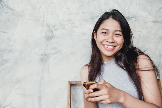 Stile di vita moderno felice, sorriso adulto dei capelli lunghi neri delle donne asiatiche isolato su bianco.