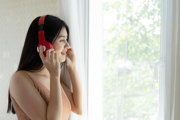 Stile di vita ragazza asiatica bella sensazione carina ragazza felice di ascoltare musica con le cuffie cuffie sulla camera da letto bianca