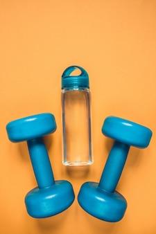 Stile di vita sano, abitudini salutari. acqua della disintossicazione, macedonia, manubri dell'attrezzatura di sport sullo spazio blu della copia di vista superiore del fondo