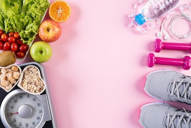 Stile di vita sano, cibo e concetto di sport su pastello rosa.