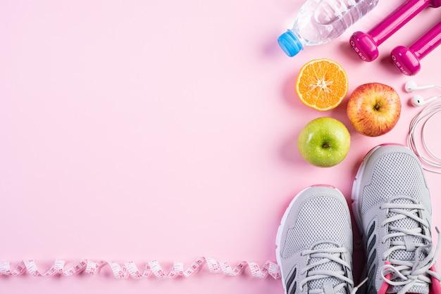 Stile di vita sano, cibo e concetto di sport su sfondo rosa pastello.