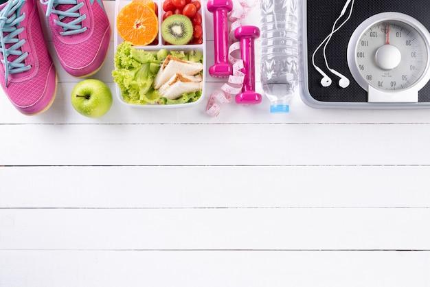 Stile di vita sano, cibo e sport su fondo di legno bianco.