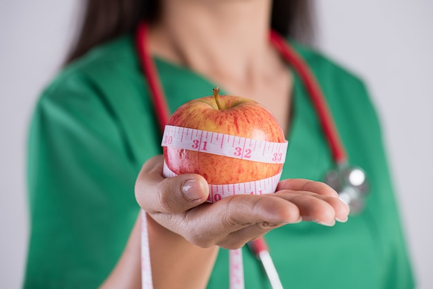 Stile di vita sano, medico che tiene il nastro di misurazione intorno alla mela verde fresca.